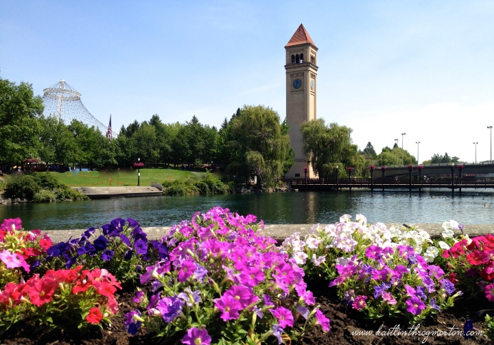 As seen from the main downtown entrance to Riverfront Park, the Clock Tower rises above patches of flowers.