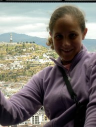My 15-year-old self leaning out of one of the towers of the Basilica Nacional in Quito, Ecuador, with the Panecillo in the background.