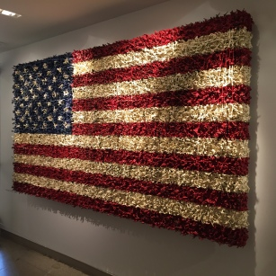 An American flag made of small green army men toys.