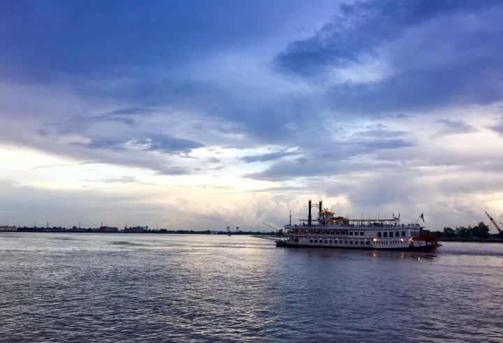 Ferry boat on the Mississippi River in New Orleans with a cloudy blueish sky and fading sunset